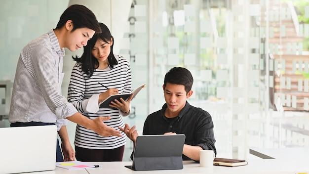 Discussione di giovane impresa con tablet in ufficio moderno.