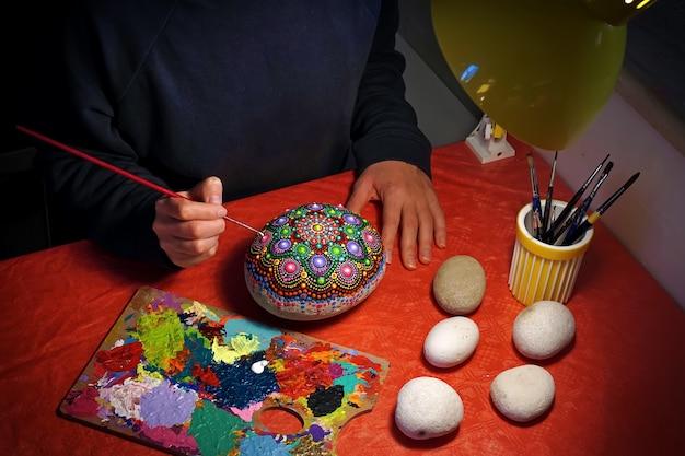 Disegnando con un pennello un mandala su una pietra
