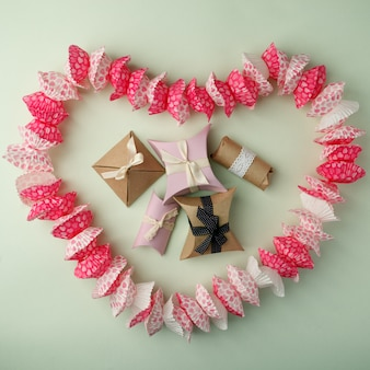 Disegnato a forma di cupcake a forma di cuore e scatole regalo su uno sfondo verde pastello, copia spazio, alto, vista
