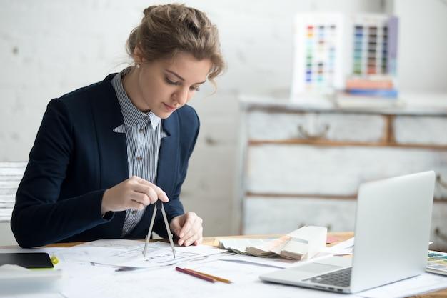 Disegnatore femminile utilizzando la bussola di disegno