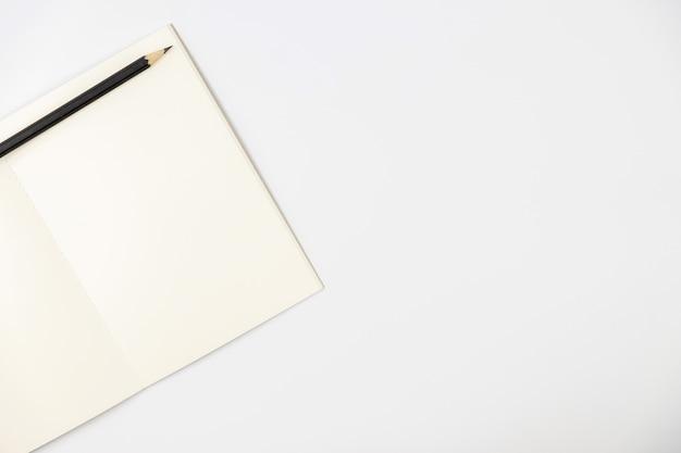Disegni a matita sul libro vuoto su priorità bassa isolata bianca, copi lo spazio