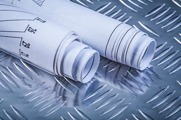 Disegni di costruzione rotolati sulla vista frontale del fondo scanalato del metallo
