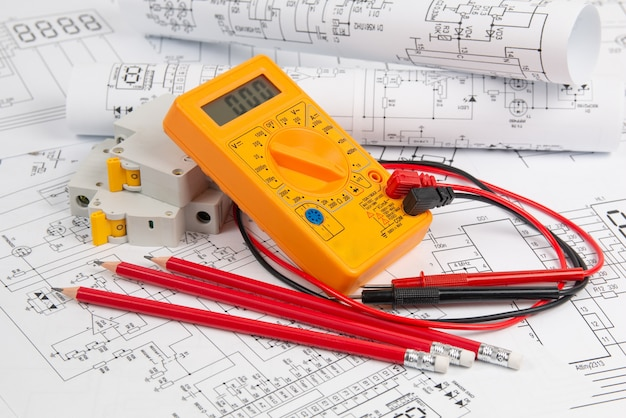 Disegni di ingegneria elettrica, interruttore, matite e multimetro digitale