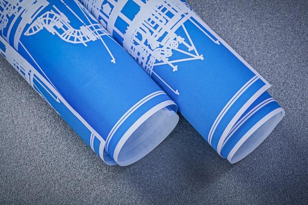 Disegni di ingegneria rotolati blu sul concetto grigio della costruzione del fondo
