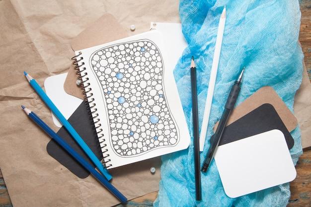 Disegni di stile zentangle in un notebook, uno sfondo in legno marrone scuro, scarabocchio