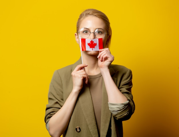 Disegni la donna bionda in rivestimento con la bandiera canadese su giallo