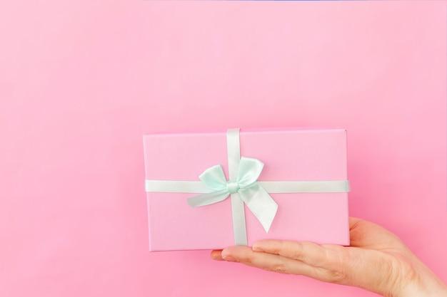 Disegni semplicemente la mano femminile della donna che tiene il contenitore di regalo rosa isolato su d'avanguardia variopinto pastello rosa