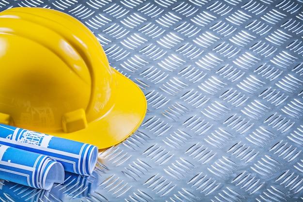 Disegni tecnici blu che costruiscono casco sulle sedere ondulate del metallo