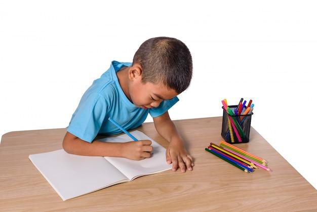 Disegno allegro sveglio del bambino facendo uso della matita di colore mentre sedendosi alla tavola isolata su fondo bianco