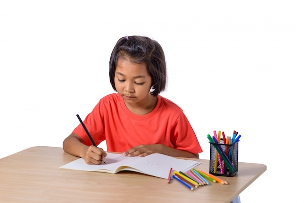 Disegno allegro sveglio del bambino facendo uso della matita di colore mentre sedendosi alla tavola isolata sul fondo bianco