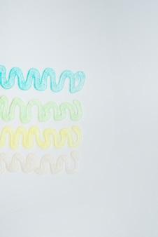 Disegno astratto realizzato con colori glitter su sfondo bianco