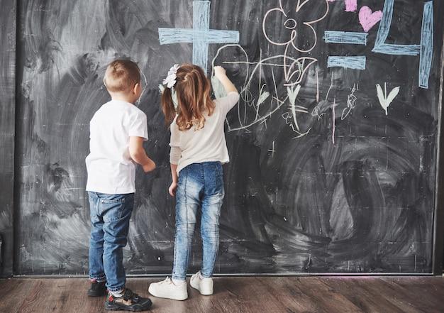 Disegno sveglio del ragazzo e della bambina con il colore del pastello sulla parete. lavoro del bambino. scrittura sveglia dell'allievo sulla lavagna