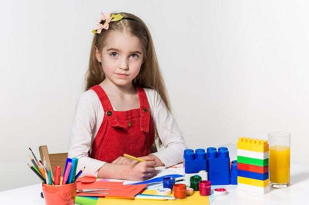Disegno sveglio della bambina con la pittura e il pennello a casa