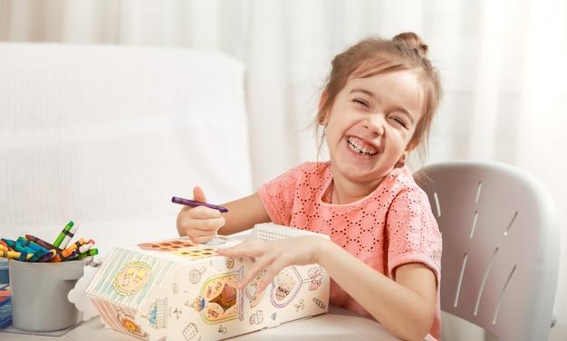 Disegno sveglio della bambina con le matite a casa