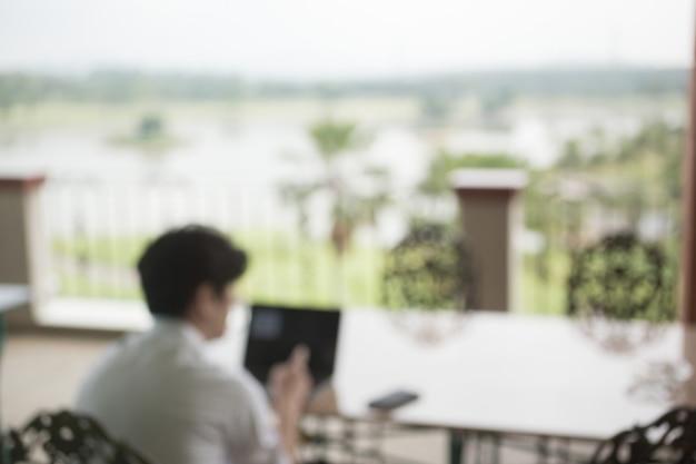 Disfocus del laptop di lavoro usinessman mentre sedendosi alla sedia con la vista esterna
