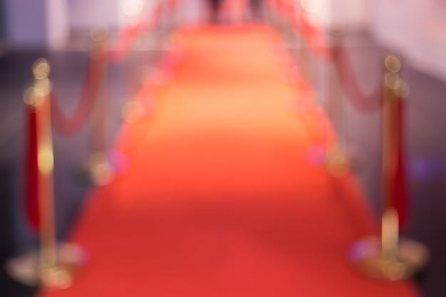 Disfocus del tappeto rosso tra le barriere della corda nella festa del successo