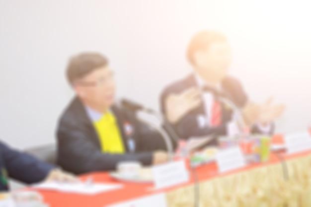 Disfocus dell'uomo d'affari che dà un discorso pubblico in una sala per conferenze