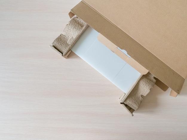 Disimballare un nuovo laptop da una scatola di cartone. disimballare il pacco ricevuto