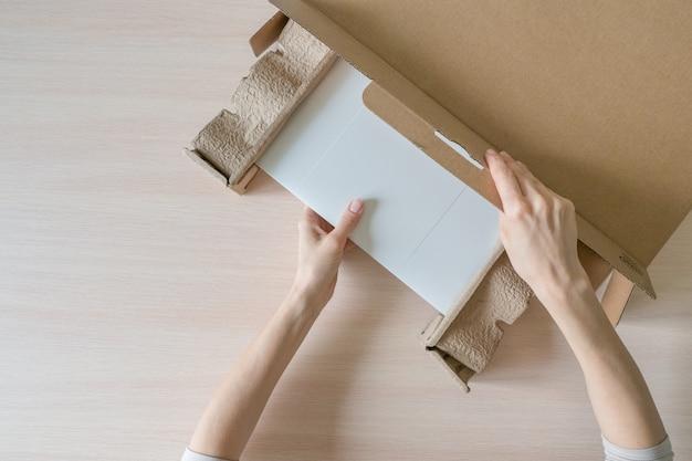 Disimballare un nuovo laptop da una scatola di cartone. le mani aprono la scatola. disimballare il pacco ricevuto