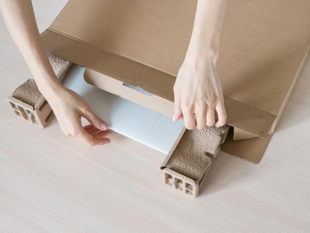 Disimballare un nuovo laptop da una scatola di cartone