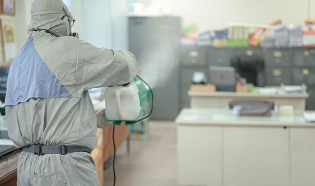 Disinfezione dell'ufficio per prevenire covid-19, persona in tuta bianca ignifuga con disinfezione in ufficio, concetto di coronavirus