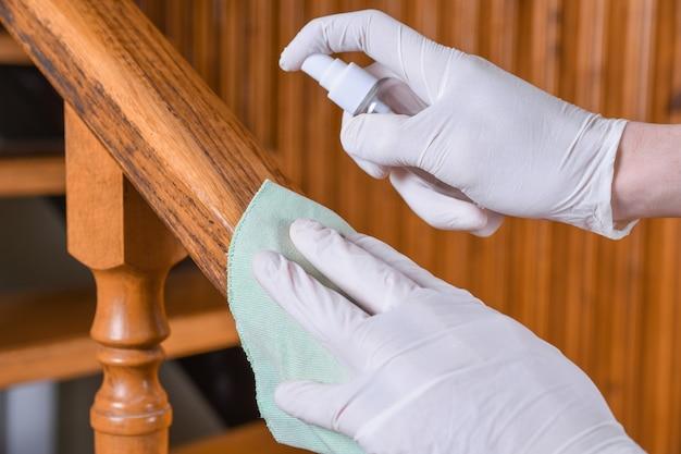 Disinfezione della ringhiera delle scale. pulizia profonda per la prevenzione delle malattie covid-19. alcool, disinfettante spray su salviette di infezione