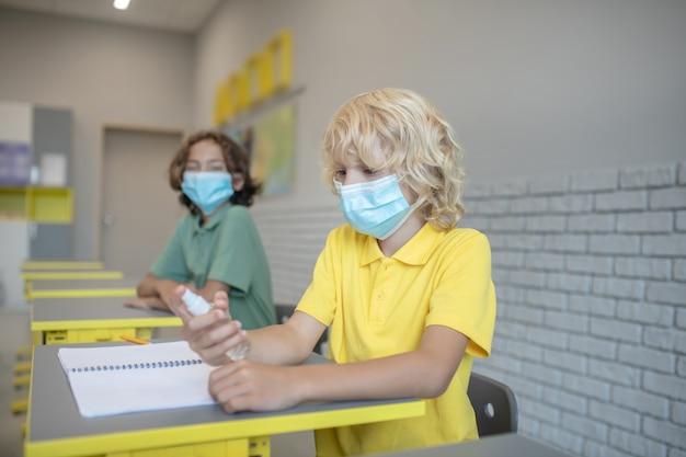 Disinfezione delle mani. ragazzo biondo in una maschera che spruzza disinfettante sulle sue mani