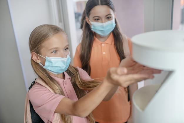 Disinfezione. ragazza bionda con maschera preventiva che si prende un disinfettante in mano