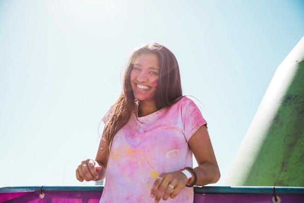 Disordine sorridente della giovane donna nel colore di holi che sta contro il cielo blu