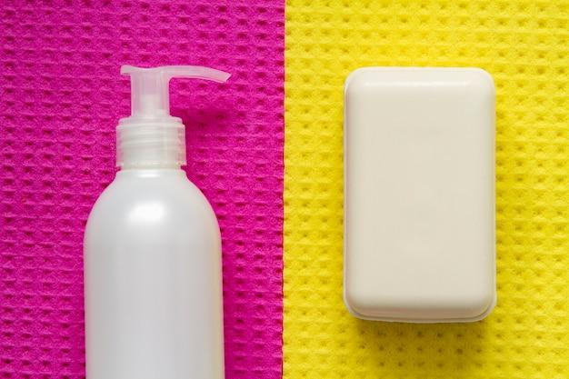 Dispenser di sapone liquido e un pezzo di sapone per protezione e prevenzione da batteri e virus su una superficie giallo-rosa