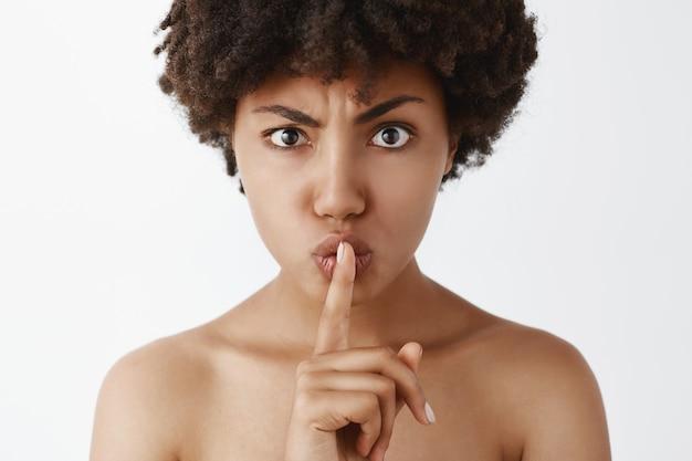 Dispiaciuta e incazzata bella donna nuda dalla pelle scura con i capelli ricci che mostra il gesto di silenzio con il dito indice sulla bocca chiedendo silenzio o mantenendo il segreto