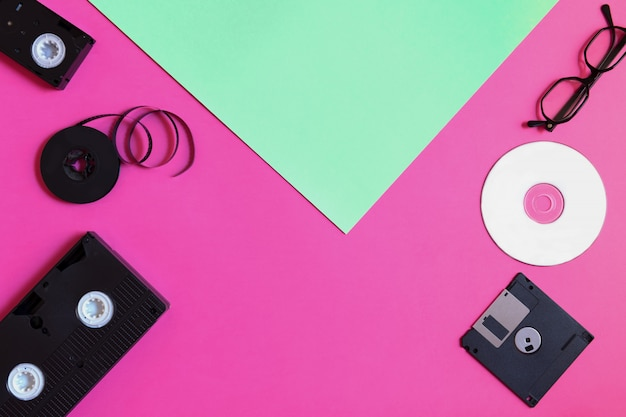 Dispositivi di archiviazione retrò: piastra, due videocassette, floppy disk, cd e occhiali.