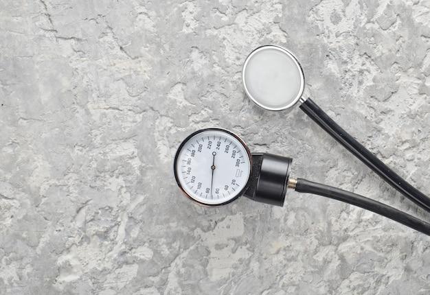 Dispositivi medici per la misurazione della pressione e stetoscopio su un tavolo di cemento. vista dall'alto.