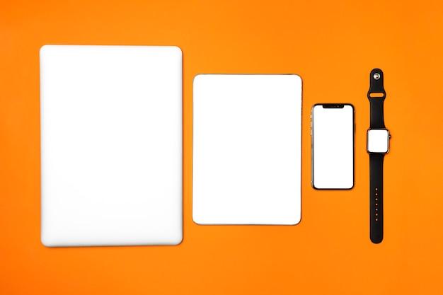 Dispositivi piatti laici su sfondo arancione