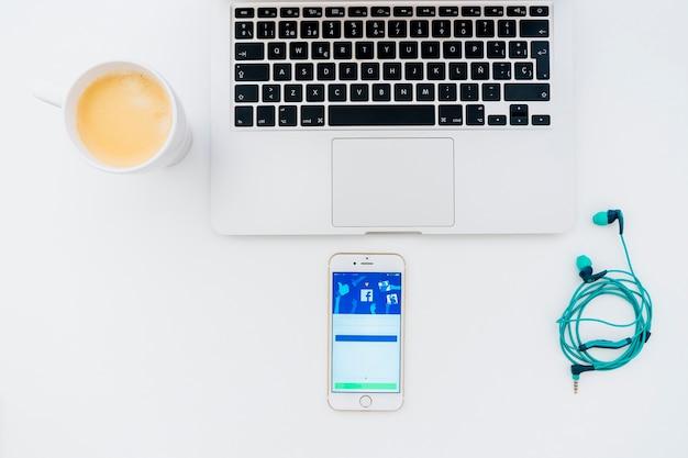 Dispositivi tecnologici, tazza di coffe e facebook