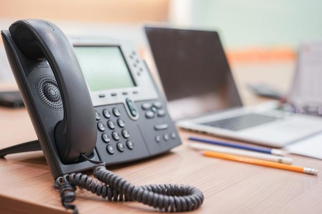 Dispositivi telefonici con notebook stazionario alla scrivania