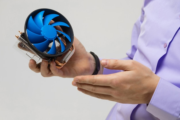 Dispositivo di raffreddamento in primo piano delle mani degli uomini isolato su fondo leggero