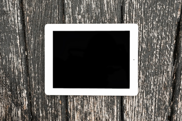 Dispositivo di tavoletta digitale vuoto sul contesto strutturato in legno