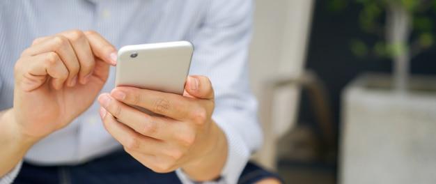 Dispositivo mobile del telefono cellulare della stretta della mano: metta a fuoco sul gioco dell'uomo sul concetto dello smartphone