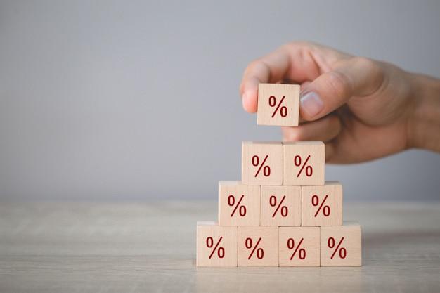 Disposizione a mano del blocco di legno impilabile con il simbolo di percentuale dell'icona verso l'alto
