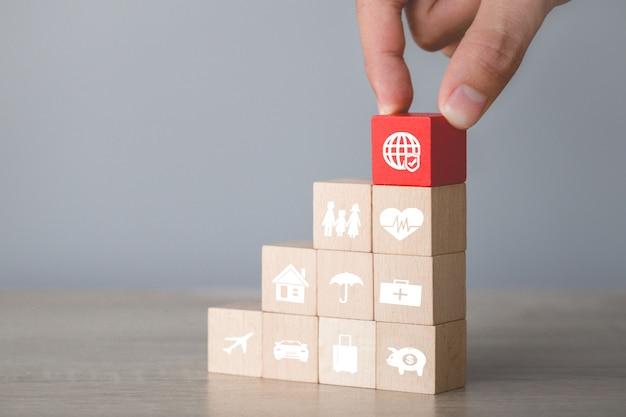Disposizione a mano di blocchi di legno impilabili con un'icona di assicurazione: auto,