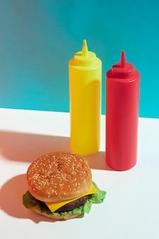 Disposizione ad alto angolo con bottiglie di hamburger e salsa