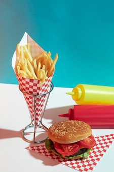 Disposizione ad alto angolo con bottiglie di salsa e hamburger