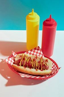 Disposizione ad alto angolo con hot dog e bottiglie di salsa