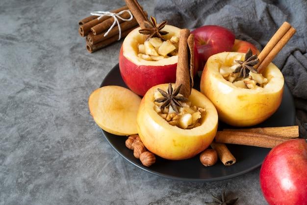 Disposizione ad alto angolo con mele cotte e bastoncini di cannella