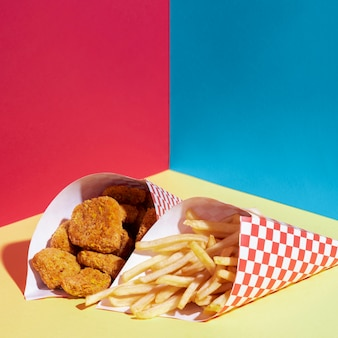 Disposizione ad angolo alto con patatine fritte e bocconcini di pollo
