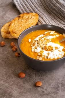 Disposizione ad angolo alto con zuppa di zucca e toast