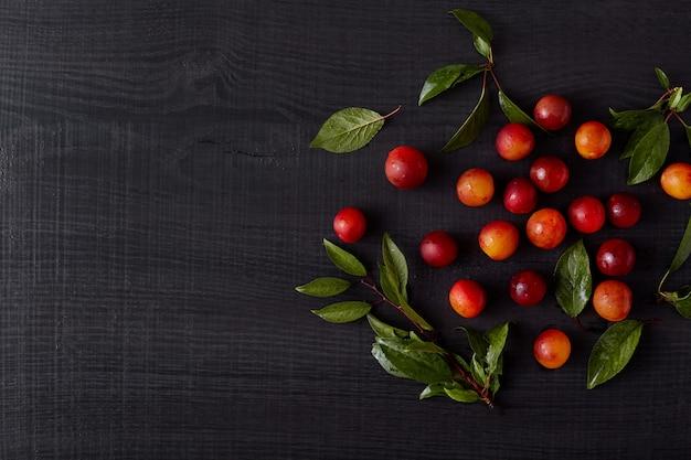 Disposizione armoniosa fatta di frutta con foglie verdi. molte prugne mature rosse rosse sono vicine l'una all'altra, con piccoli rami intorno. composizione piena nella frutta che si trova sopra il fondo nero.