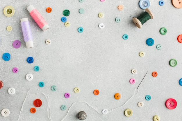Disposizione carina con filati cucirini e bottoni colorati vista dall'alto