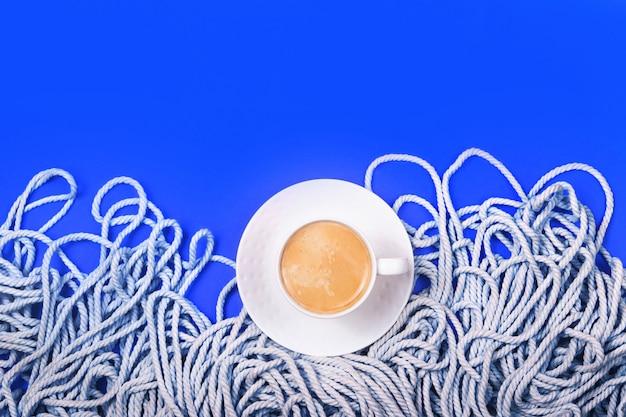 Disposizione classica blu con corda in cotone bianco minimalista e tazza di caffè.